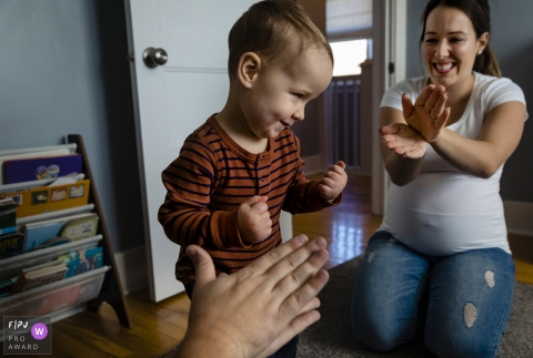 Ontario toddler makes face while dancing as parents clap - Canada family photo session at home.