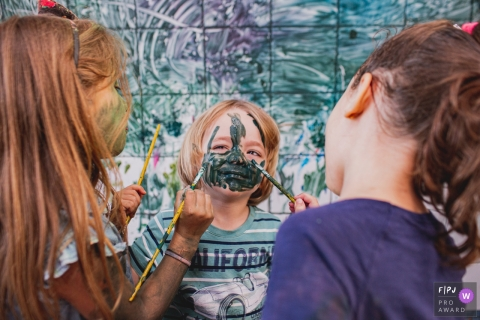 A boy gets his face painted up by two girls | Sao Paulo child photography