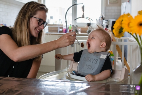 "Mother is feeding her ""always hungry"" young boy in the kitchen 