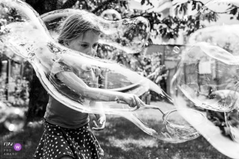 Girl wrapped in a large, long bubble while playing in the backyard | Brussels Family Photographer