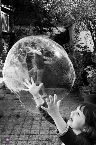 "The ""Bubble Master"" girl with an oversized bubble, playing in the backyard 