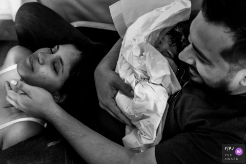 Mother relaxes after giving birth as father holds the new little one | Venezuela Birthing Photography