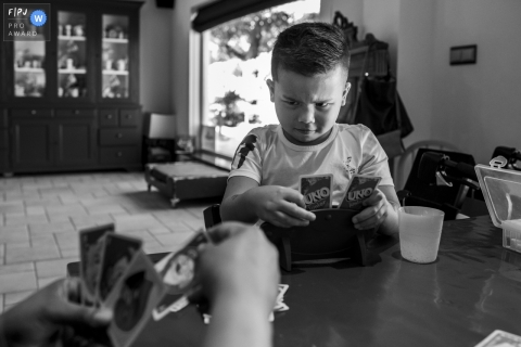 Young boy with a serious face during a game of Uno with the family | Netherlands Family Photo