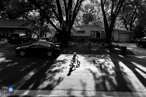 Wisconsin family photography | Child rides his bike in street on a summer's day.