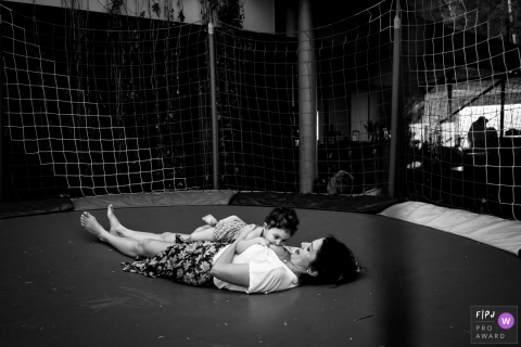 Mother breastfeeds baby on trampoline at home | Santa Catarina family photography