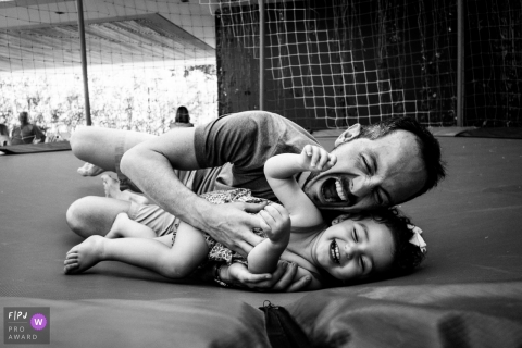 A playful father plays with his daughter in a trampoline | Brazil family photographer