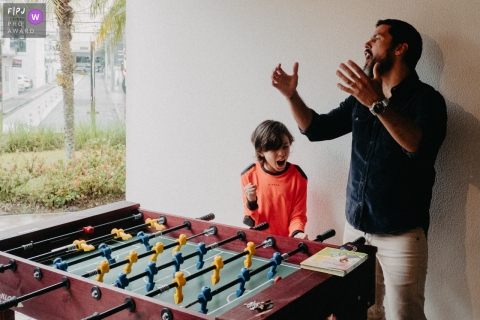 Father and son celebrating together after a game of foosball.