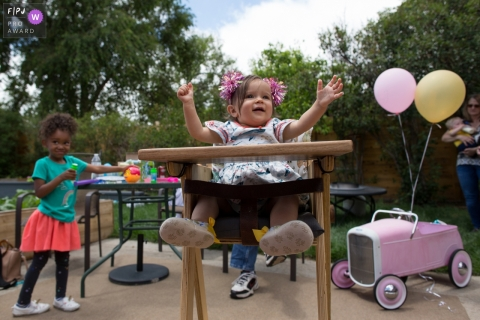 Colorado family photo of a 1st birthday kid cheering in her high chair