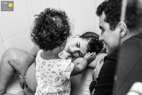 In Rio de Janeiro Brazil During labor, the pregnant woman receives the affection of her eldest daughter, beside her father