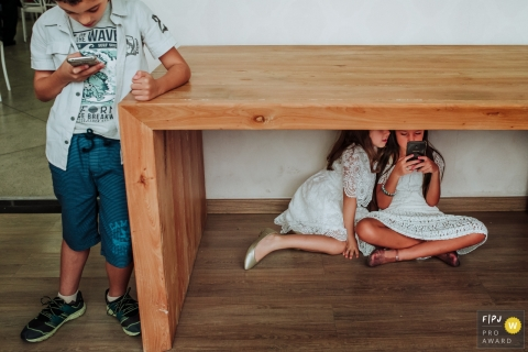 Minas Gerais Family Photography | Two girls under a table on a mobile device, with boy off the side also with a phone.