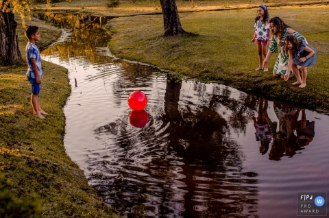 Minas Gerais family playing with a big red ball that fell into a creek that is hard to reach from the water edges.