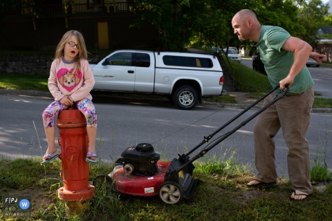 British Columbia father mows the lawn has his daughter sits on a fire hydrant.