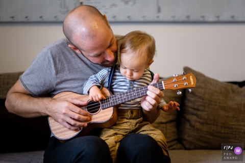 Berlin Germany child Enthralled with dad and the guitar