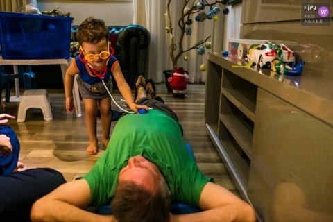 Belo Horizonte Minas Gerais boy plays being a doctor examining his father