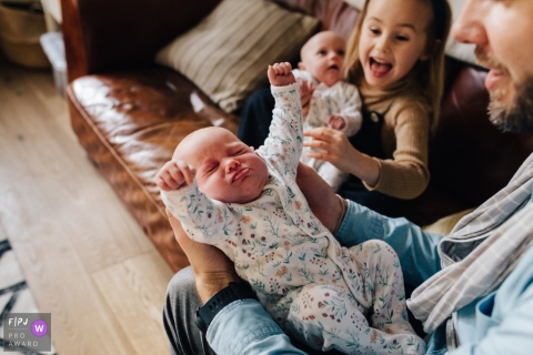 London England Baby twin stretching at home with dad and big sister