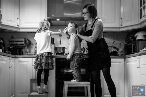 Cambridgeshire England Mum wipes boy's nose while he cooks with sister