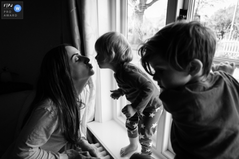 Cambridgeshire England Mum kisses toddler on window sill