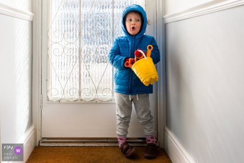 Kent England Little girl waits by the door in big winter coat holding bucket and spade