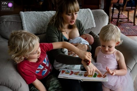 Kent	England Nursing mother and daughter read a book while big brother plays cars on mum