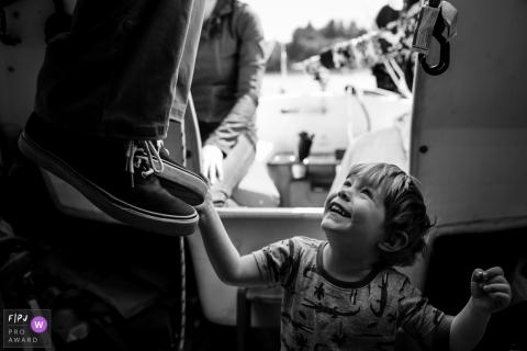 Washington young boy pulls at fathers shoes while sailing boat