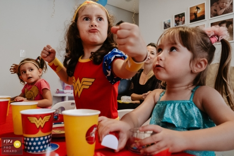 Birthday girl, playing superhero with friends, celebrating at home in Santa Catarina, Brazil.