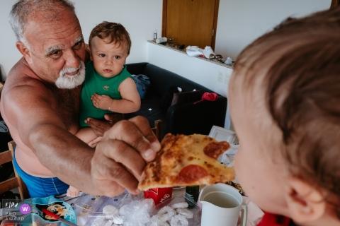 Florianopolis Santa Catarina man feeding a child pizza
