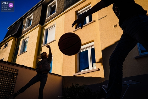 Silhouette of children playing basketball with a brightly sunlit building behind them | Germany kid sports photography