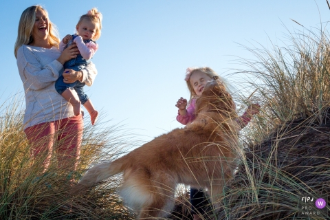 Girl gets a big kiss from her dog as she walks at the beach with her family | Ventura Family Photography