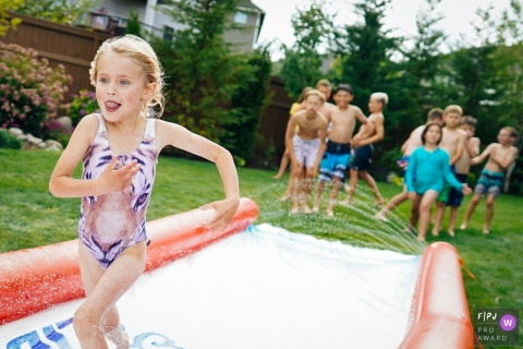 Washington family and kid photography   girl runs down a water slide as others are waiting for their turn