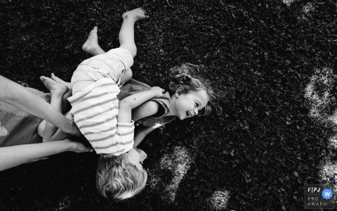 French family photographer captures two kids playing around on the grass.
