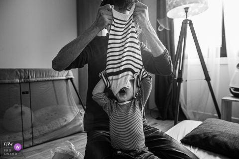 Toddler with his head still in his sweater that daddy's taking off. |  France family day in the life photography