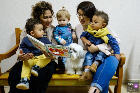 Family sit on a bench reading a book during a Sao Paulo family photo session