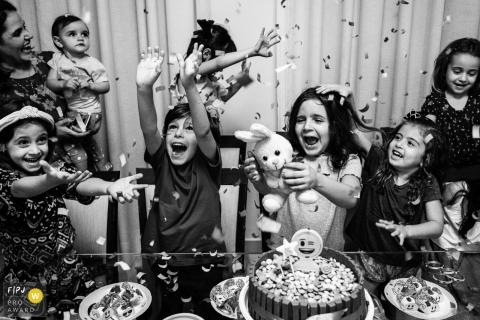 Kids having a blast during a birthday party with lots of confetti flying | Sao Paulo birthday party photographer