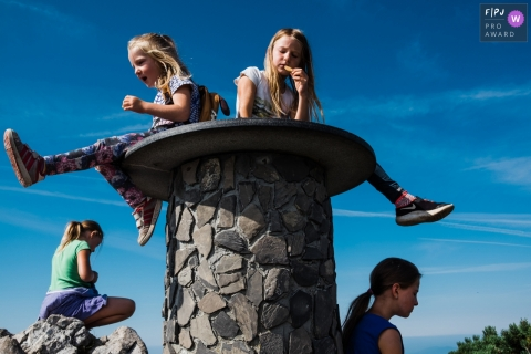 A couple of girls sitting on a pedestal on top of a hill with other family | Slovenia family photo