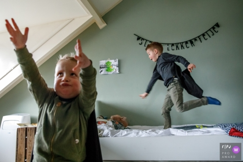 Superhero boys play in their room during a family photo shoot in the Netherlands