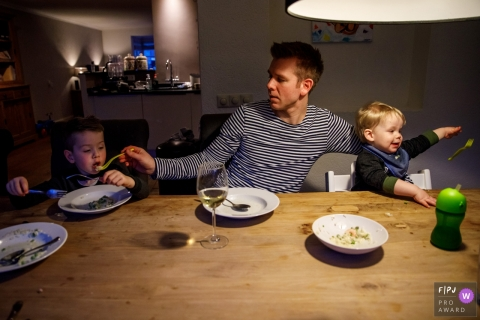 Dad sits with his two boys at the dinner table and helps with feeding one of them | Netherlands Day in the Life Photographer