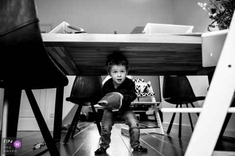 Boy helps mom out by using a hand vacuum to do some cleanup under the table  | Eindhoven family photography
