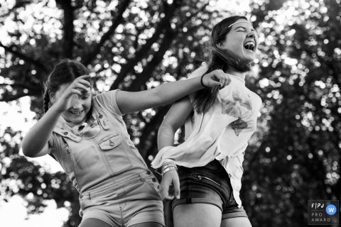 Two girls having fun bumping hips and laughing | Belgium Family Photographer
