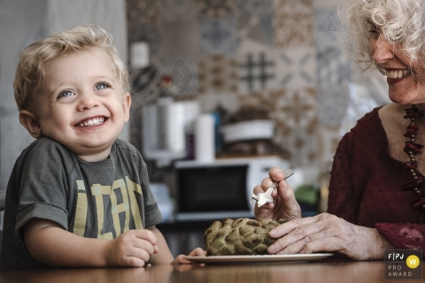 Image captured of a young boy thoroughly enjoying his lunch with grandma | Rio de Janeiro family photography