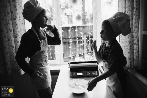 Kids licking the bowl while cooking with aprons and chef hats during a family photo session in Russia.