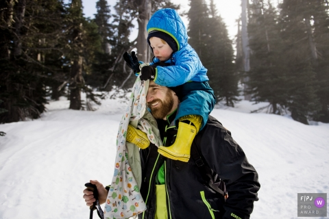 A winter Washington family photo of a father giving his kid a piggy back ride while snowshoeing