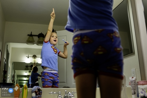 Boy playing superhero in the mirror while getting ready to brush his teeth | Key West Day in the Life Photographer