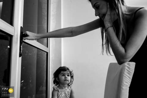 Mato Grosso family photographer captures a mother closing a door to the outside while a young girl watches.