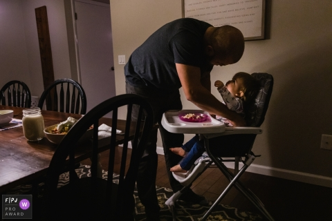 baby girl looks up at and reaches up for her dad as he buckles her into her high chair in their PA home.