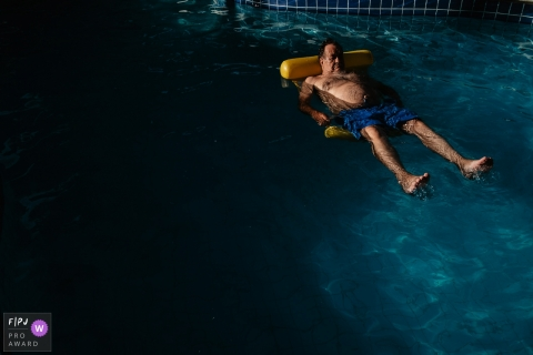 Brazilian photographer captured a grandfather lying on a float in the pool, on vacation, quietly.