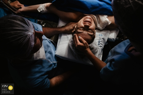 mother with an expression of gratitude and satisfaction, right after the birth of her child. Hand in hand with father and doctor | Maternidade Santa Helena birth photography