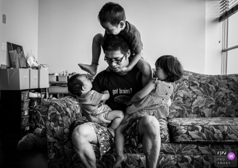 Chicago Documentary Family image of dad with his kids sitting and climbing on him