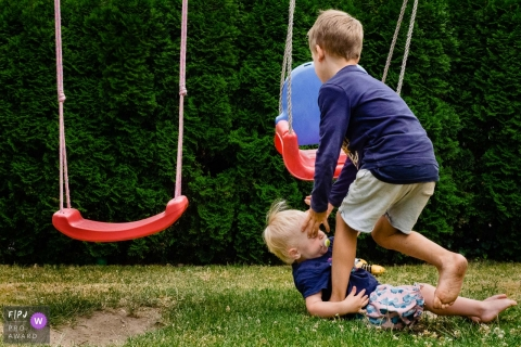 NRW Documentary Family Photography | a boy arrives to help his toddler brother after slipping off the swing and landing to the ground