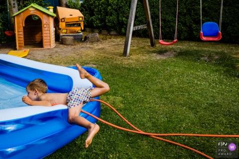 Düsseldorfer Dokumentarfilm Familienaufnahme eines Jungen, der kurz davor steht, mit dem Kopf voran in den Pool zu gehen