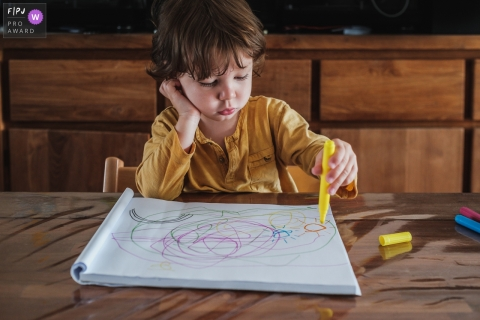 Little boy coloring at the table during this documentary family session in Belgium